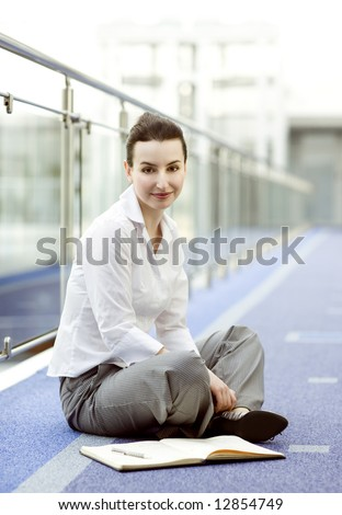 Businesswoman is sitting on the floor with a calendar beside her - stock photo