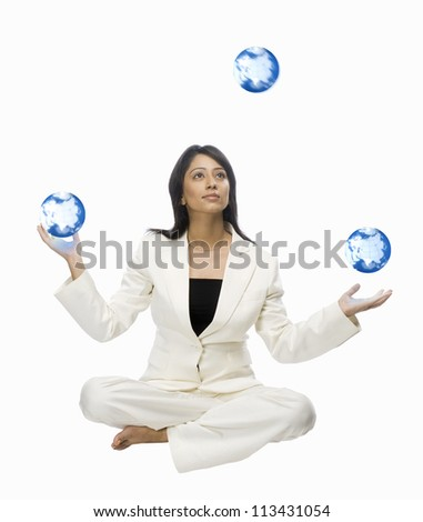 Businesswoman juggling globes - stock photo