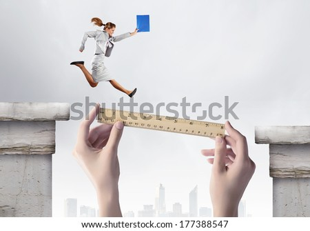 Businesswoman jumping over gap. Risk and challenge concept