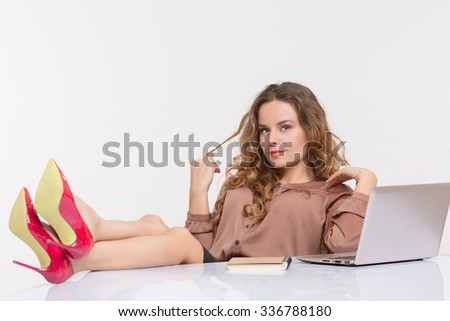 Businesswoman keeping her legs on high red heels on the table while resting and relaxing in the office. Pretty lady touching her curly hair and posing for photographer. - stock photo