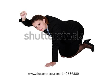 Businesswoman kneeling on the floor and holding up her fist - stock photo
