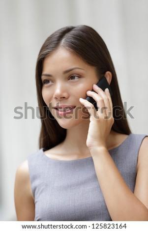 Businesswoman lawyer talking on smartphone outside. Beautiful young multiracial Caucasian / Asian Chinese professional woman. - stock photo
