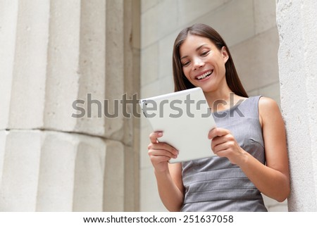 Businesswoman lawyer using tablet pc computer outside in front of courthouse smiling happy looking at camera. Beautiful young mixed race Caucasian / Asian Chinese professional woman. - stock photo
