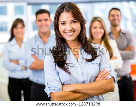 Businesswoman leading a business team and smiling - stock photo