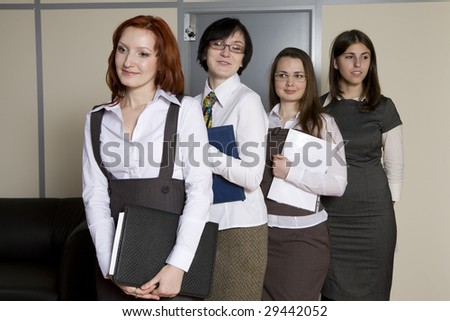 Businesswoman leading a business team in an office smiling. Secretaries standing in line for report