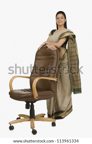 Businesswoman leaning against an office chair - stock photo