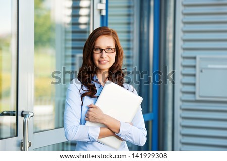 Businesswoman leaning on the door and holding a laptop - stock photo