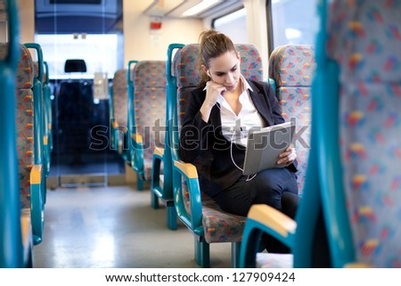 Businesswoman listening to music and using tablet computer on the train - stock photo