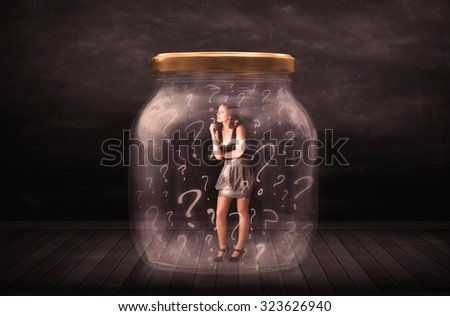 Businesswoman locked into a jar with question marks concept on background - stock photo