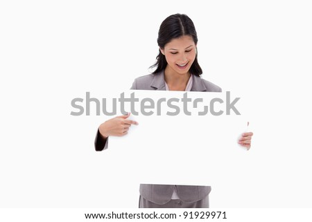 Businesswoman looking and pointing at blank sign board against a white background