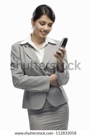 Businesswoman looking at a mobile phone against a white background - stock photo