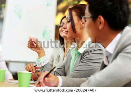 Businesswoman looking at business card in meeting