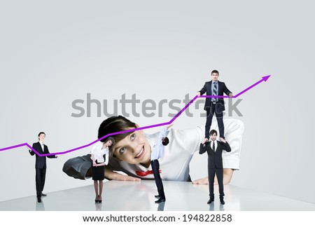 Businesswoman looking at businessteam holding increasing graph - stock photo