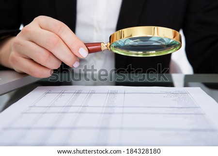 Businesswoman Looking At Document Through Magnifying Glass - stock photo