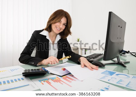 Businesswoman Looking At Financial Report Through Magnifying Glass