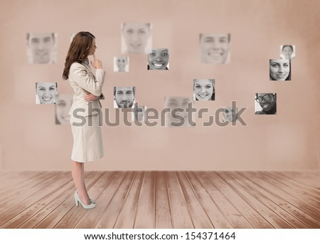 Businesswoman looking at futuristic interface in black and white showing faces - stock photo