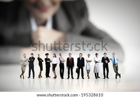 Businesswoman looking at group of businesspeople in miniature - stock photo