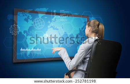 Businesswoman looking at interface with world map, graph and other elements. on blue background - stock photo