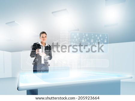 Businesswoman looking at media hologram above table - stock photo