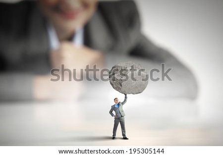 Businesswoman looking at miniature of businessman lifting stone above head - stock photo