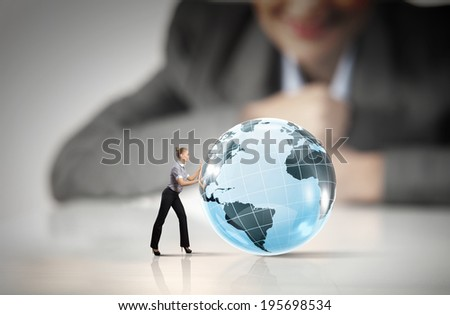 Businesswoman looking at miniature of woman rolling Earth planet