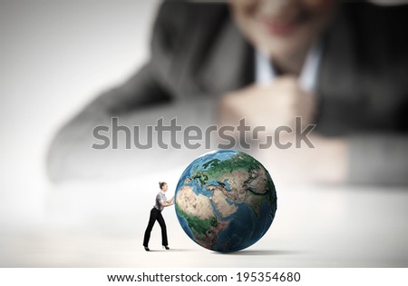 Businesswoman looking at miniature of woman rolling Earth planet. Elements of this image are furnished by NASA - stock photo