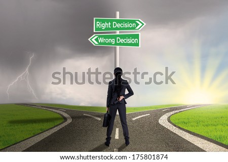 Businesswoman looking at sign of right vs wrong decision on highway - stock photo