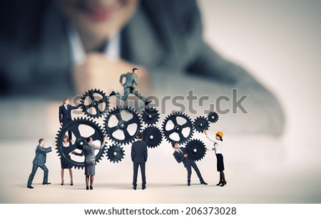 Businesswoman looking at team of businesspeople in miniature - stock photo