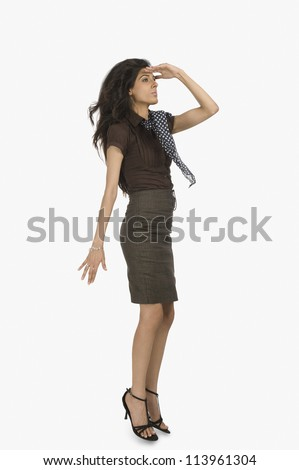Businesswoman looking away with shielding her eyes - stock photo