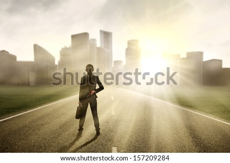 Businesswoman looking for a future and standing on the highway of a skyscraper with cityscape - stock photo