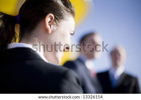 businesswoman looking forward with two businessmen looking at camera - stock photo