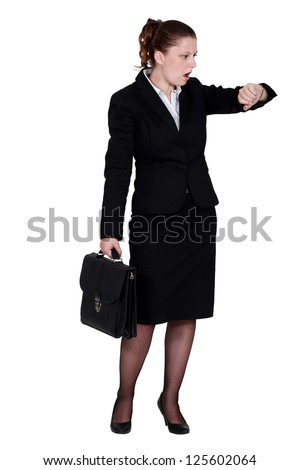 Businesswoman looking in shock at her watch - stock photo