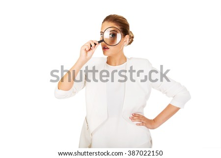 Businesswoman looking into a magnifier and have a big eye  - stock photo
