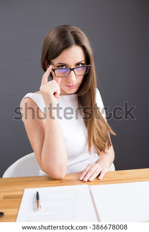 Businesswoman looking suspiciously or thoroughly over glasses reading agreement papers. Young attractive woman with dark long hair having negotiations