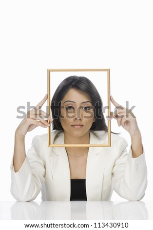 Businesswoman looking through a picture frame