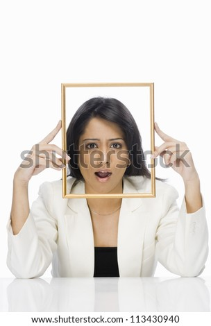 Businesswoman looking through a picture frame - stock photo