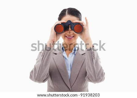Businesswoman looking through binoculars against a white background - stock photo