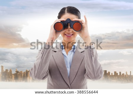 Businesswoman looking through binoculars against large city on the horizon