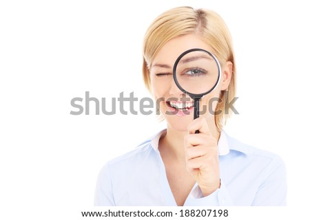 Businesswoman looking through magnifier over white background