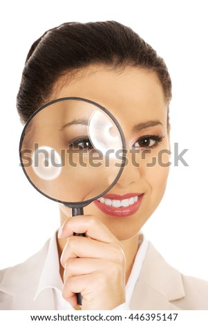 Businesswoman looking through magnifying glass.