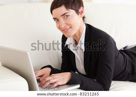 Businesswoman lying on a sofa with a laptop in the living room