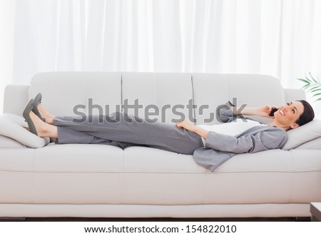 Businesswoman lying on sofa calling with her mobile phone at office