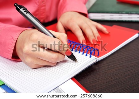 Businesswoman makes a note in notebook - stock photo