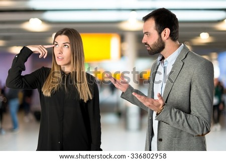Businesswoman making a crazy gesture over unfocused background