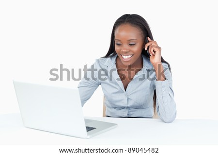Businesswoman making a phone call while using a notebook against white background - stock photo