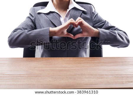 Businesswoman making heart shape hand gesture at the desk.