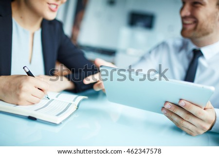 Businesswoman making notes in notebook with businessman using touchpad