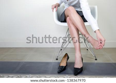Businesswoman massaging her foot - stock photo