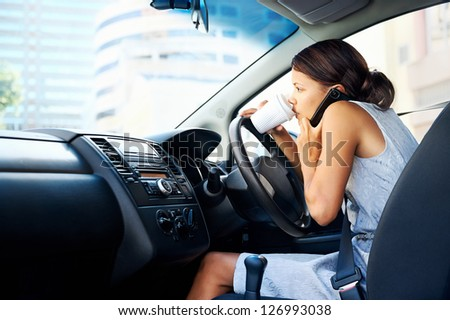 Businesswoman multitasking while driving, drinking coffee and talking on the phone - stock photo