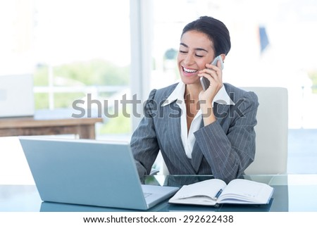 businesswoman on call and using her laptop in an office - stock photo